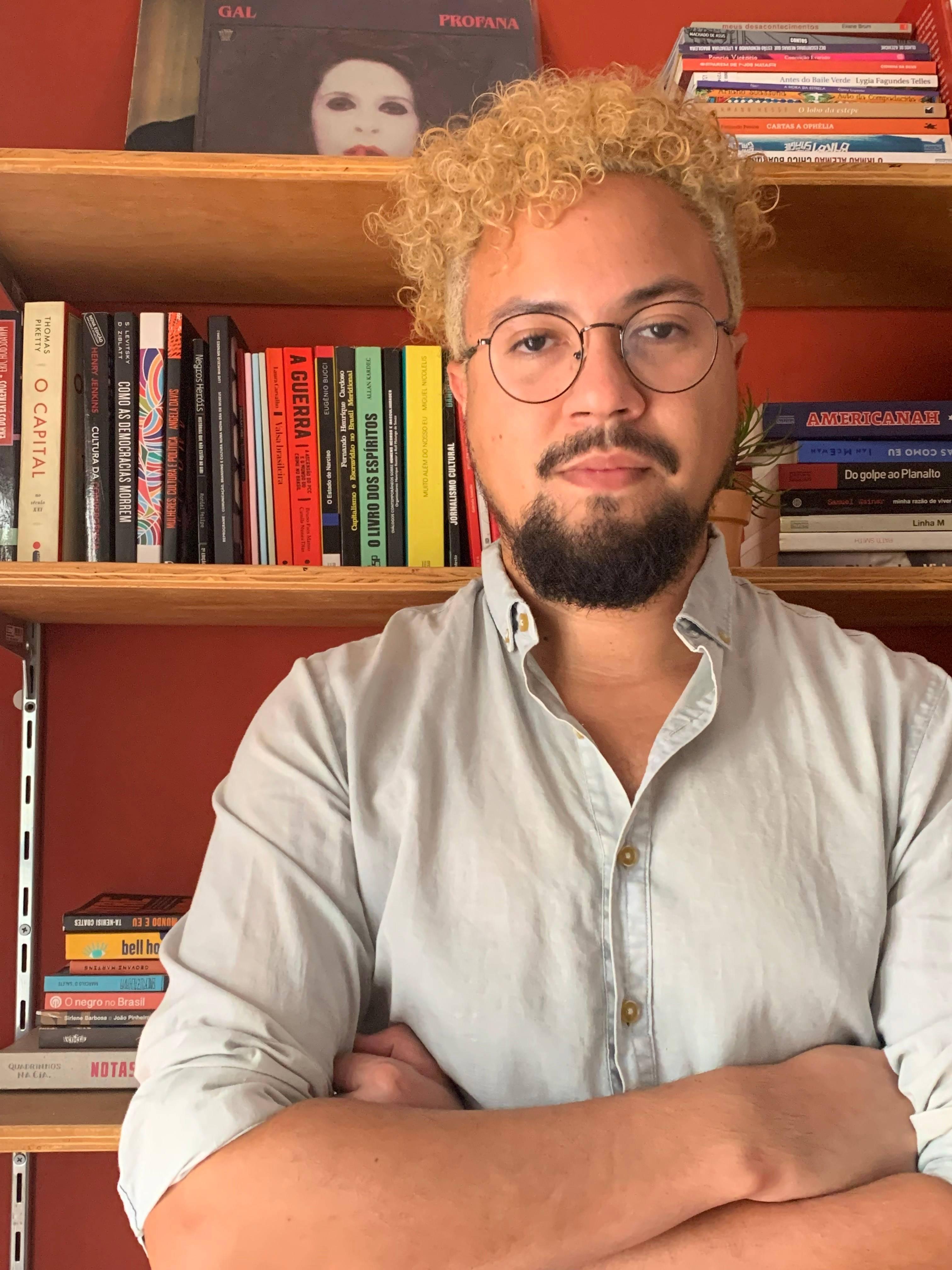 Raul Perez posa de óculos e cabelos encaracolados descoloridos em frente a estante de livros.
