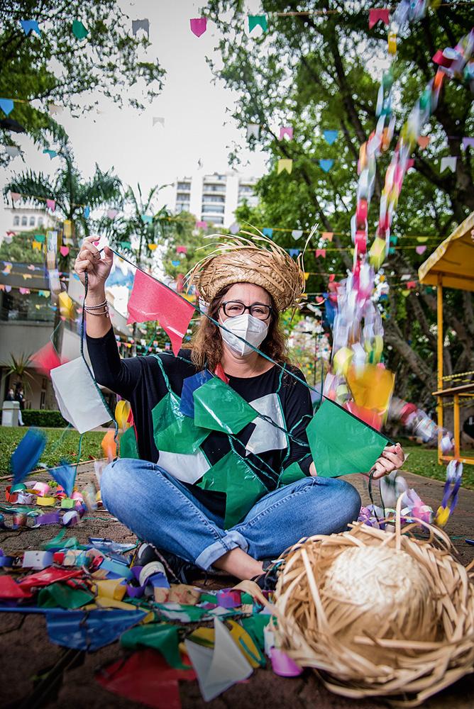 Mulher de máscara sentada com pernas cruzadas mostra bandeirinhas coloridas de festa junina