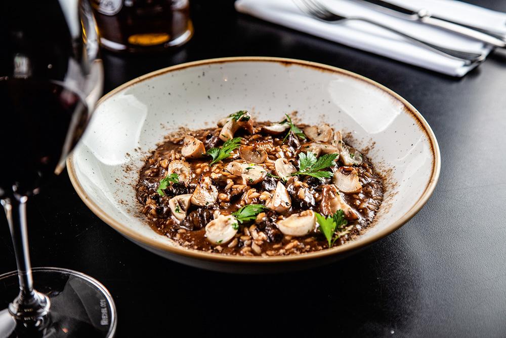 Prato fundo com risoto de cogumelos ao lado de taça de vinho tinto.