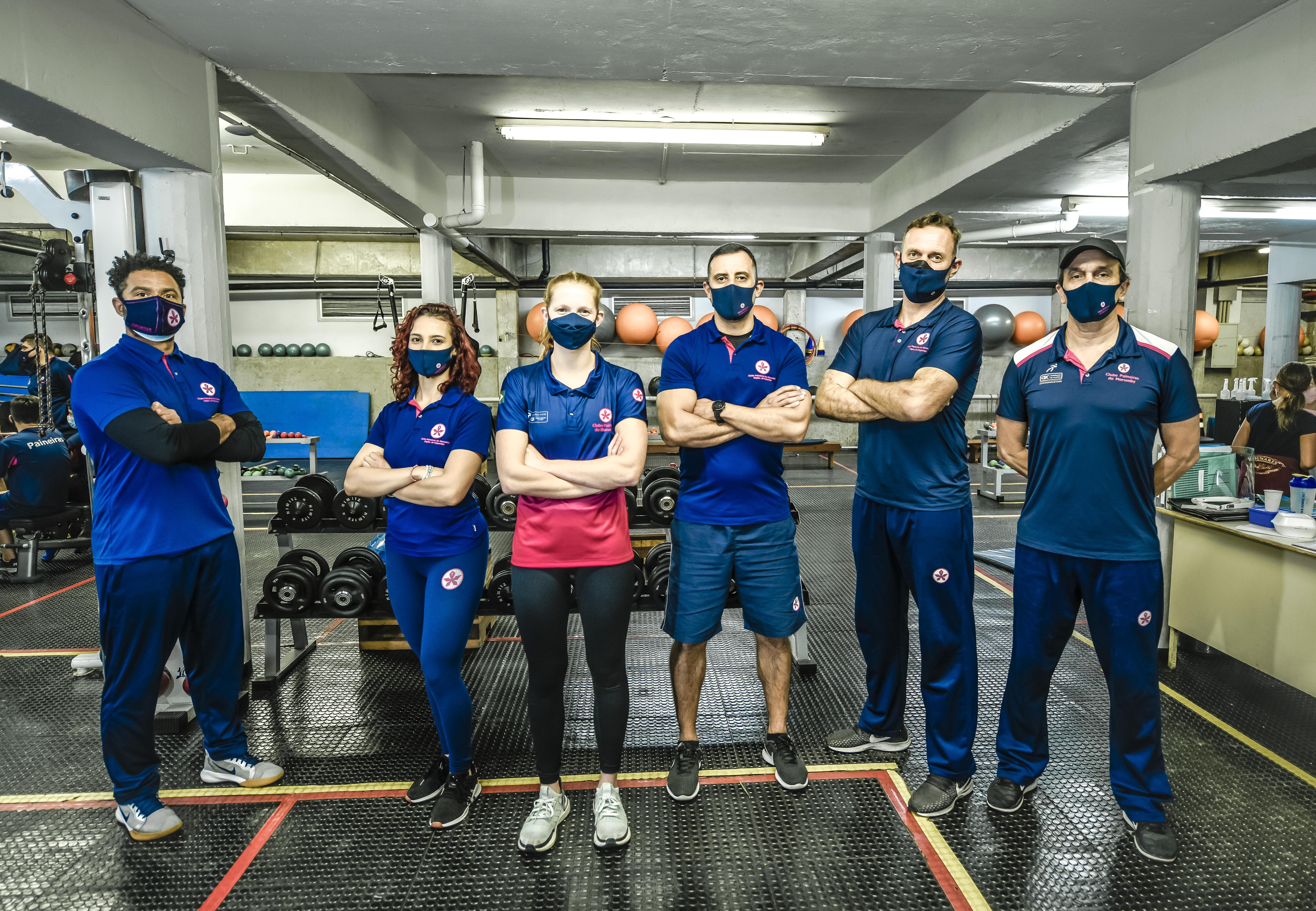 A imagem mostra Stephanie e outras pessoas com uniforme do Paineiras em uma academia, todos de máscara e braços cruzados