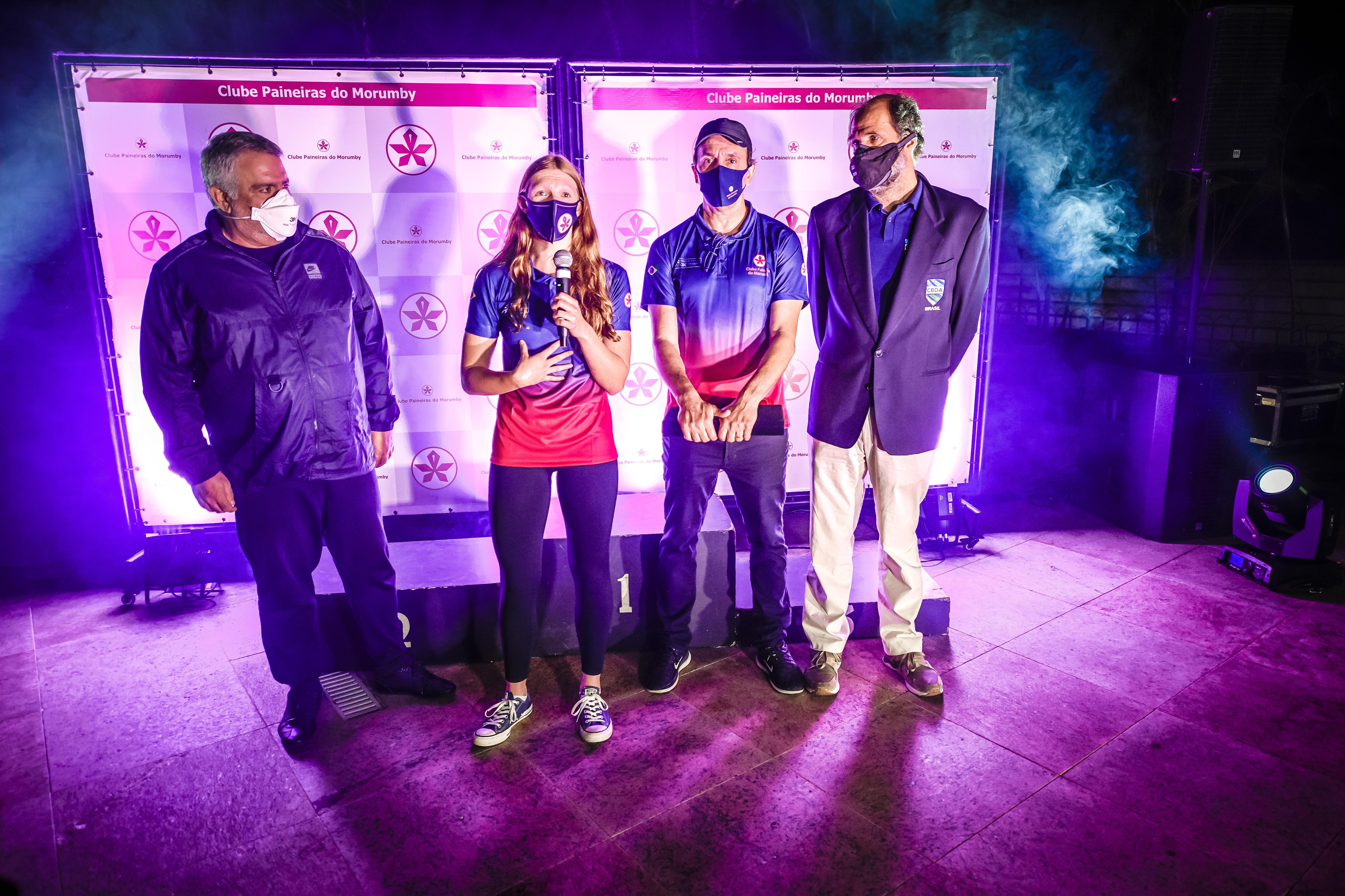 A imagem mostra Stephanie discursando com um microfone junto de outras três pessoas, todas de máscara, em área externa do clube Paineiras.