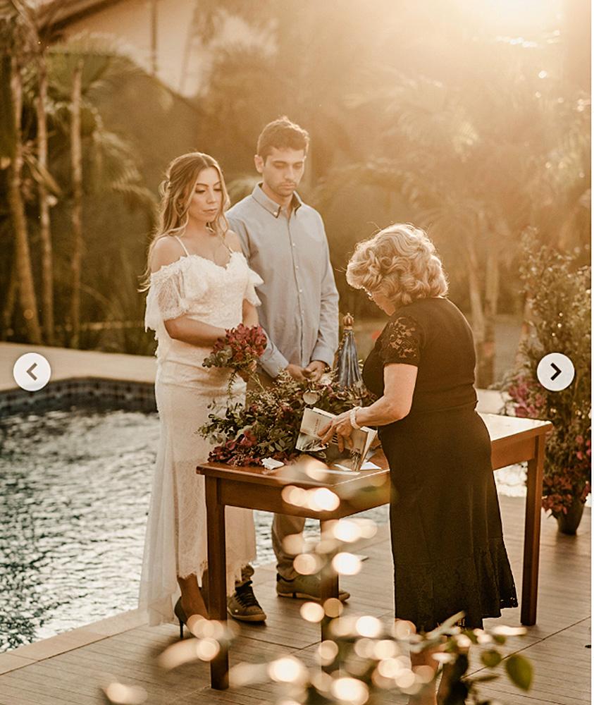 Em frente a uma piscina, dois noivos, um homem e uma mulher, estão em frente a uma senhora cerimonialista. Uma mesa com decorações separa eles