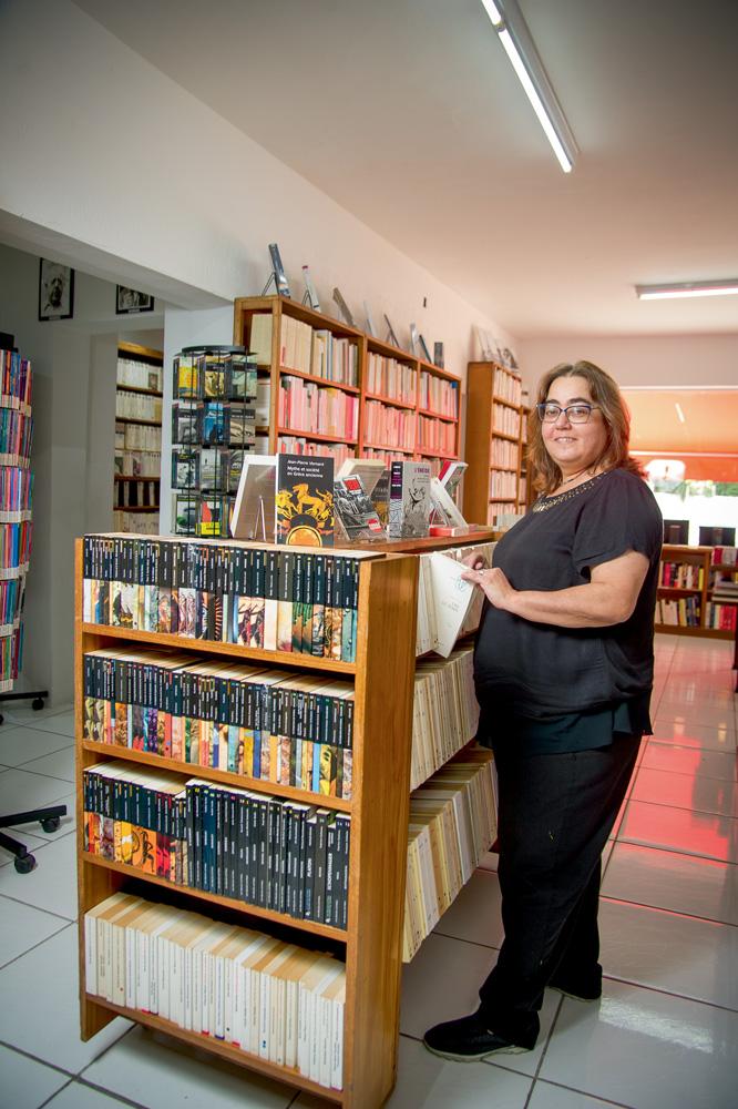 A imagem mostra Sílvia, em uma livraria, de pé em frente à uma estante enquanto sorri para a câmera retirando um livro