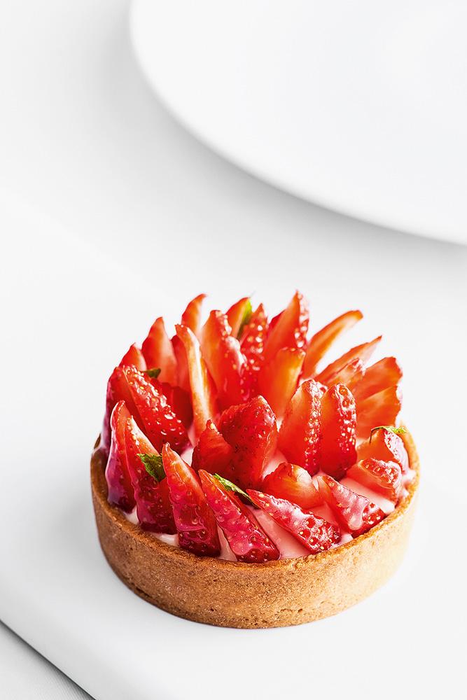 Torta pequena de morango no centro da imagem com um fundo branco.