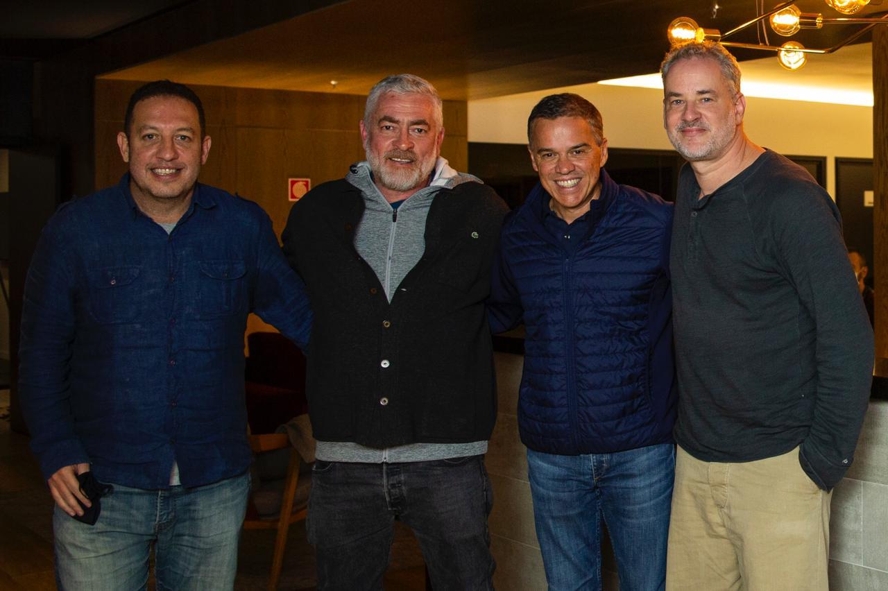 A partir da esquerda, Teco Medina, Alex Atala, Caio Mesquita e Dan Stulbach posam abraçados olhando para a câmera em um ambiente fechado.