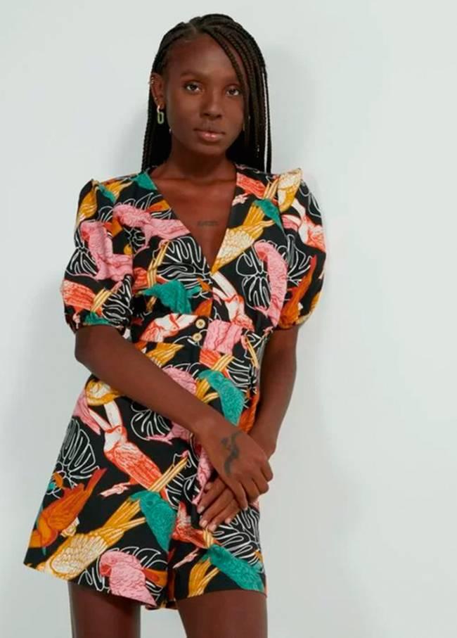 Uma mulher negra veste um macaquinho com decote V com estampa de folhas e pássaros colorida