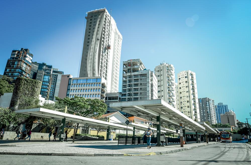 A imagem mostra prédios atrás da Vila Madalena, alguns ainda em construção. A perspectiva é de dentro do terminal de ônibus.