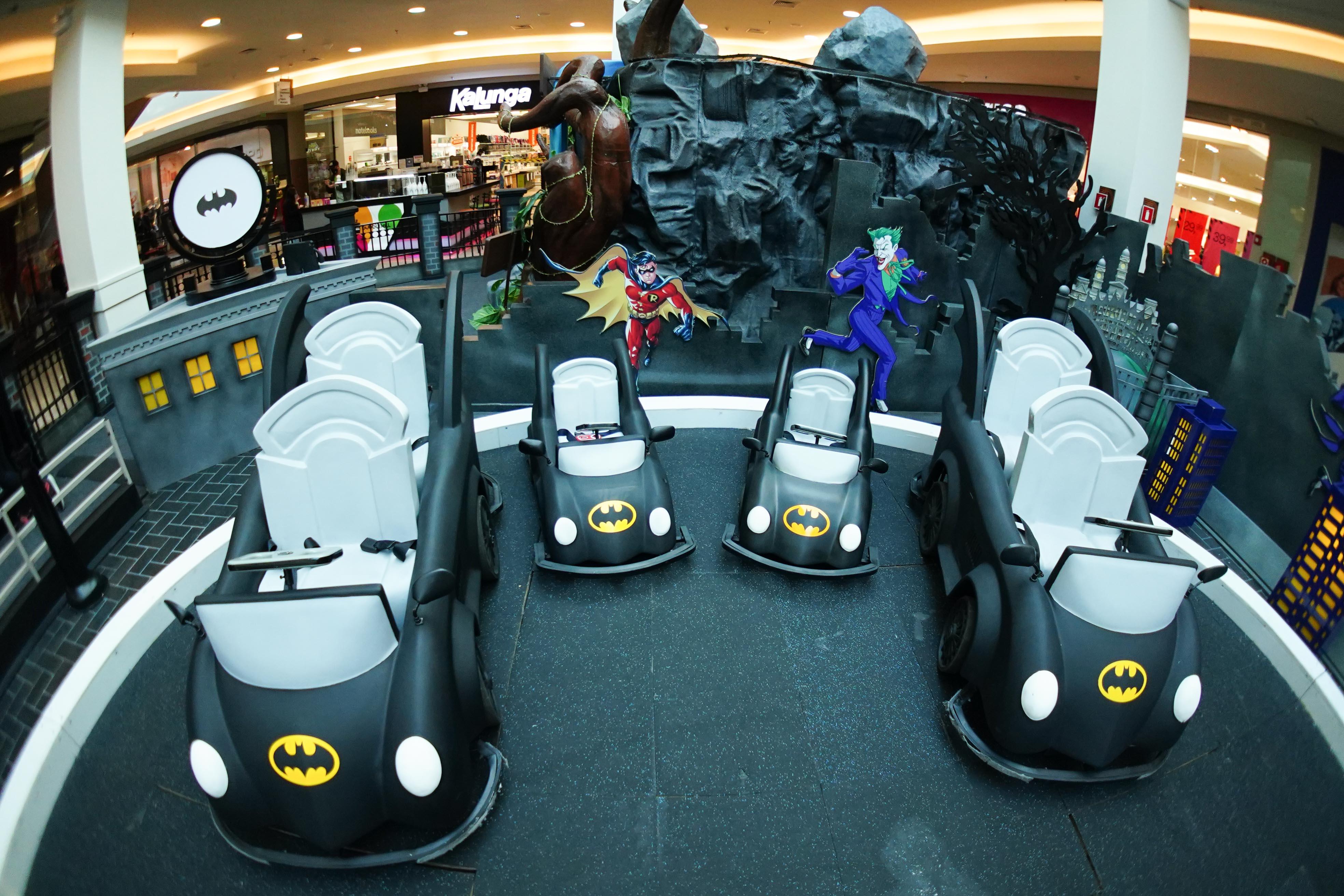 Carrinhos elétricos pretos com o símbolo do batman estão estacionados em um cenário do filme do personagem no shopping Mooca Plaza