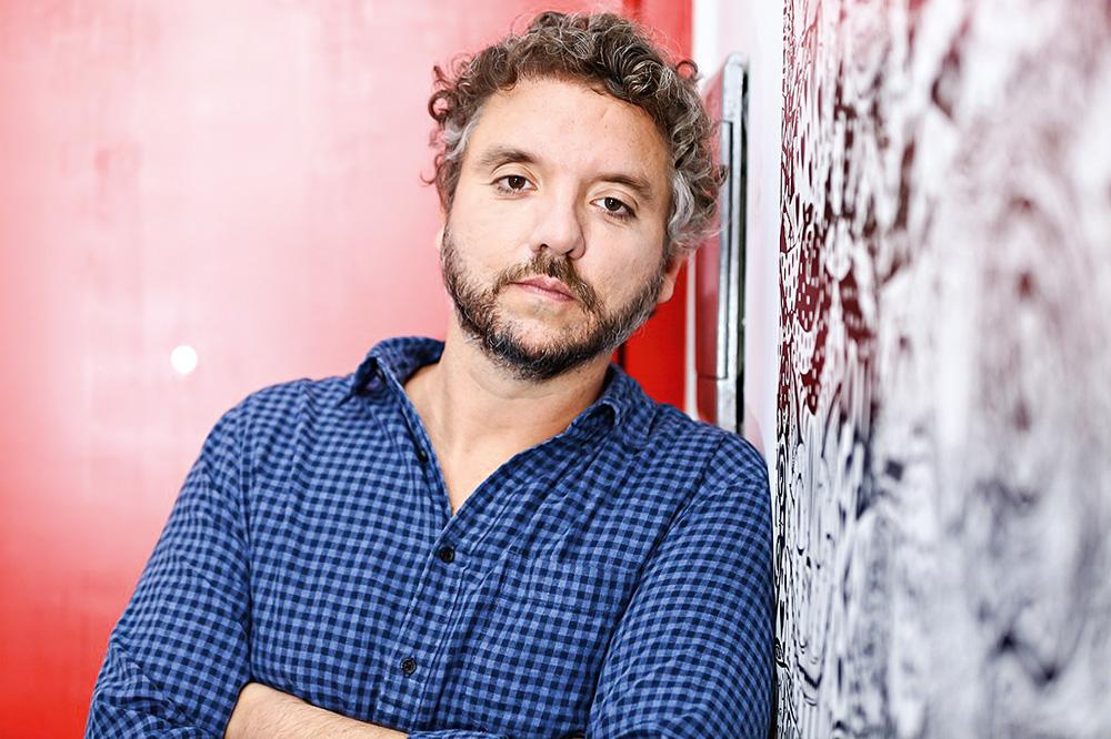 alexandre dip olhando com expressão séria para a câmera de braços cruzados e apoiado em uma parede