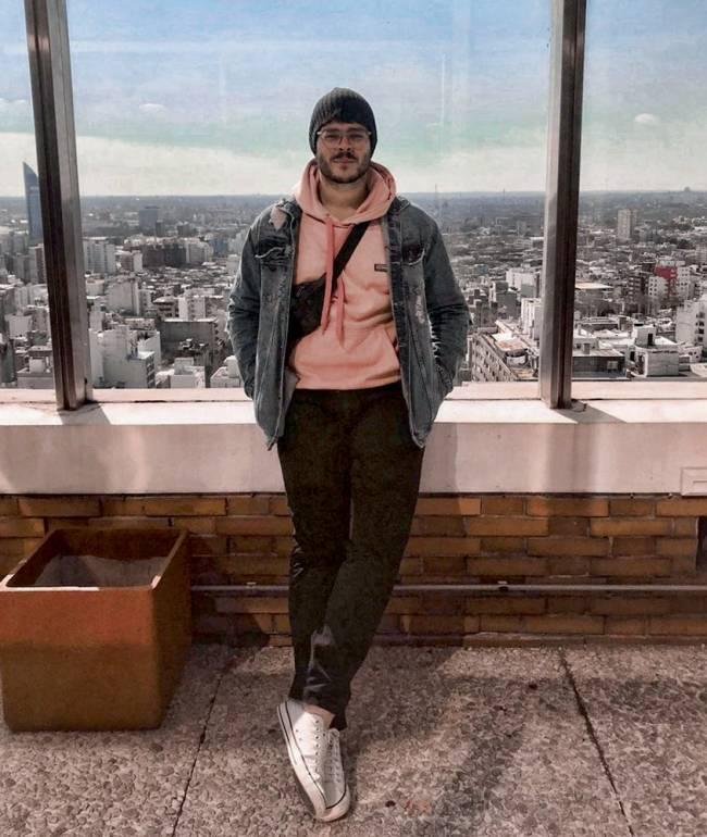Homem posa em um prédio bem alto que ao funda dá para ver todo uma cidade. Ele está com roupas de frio