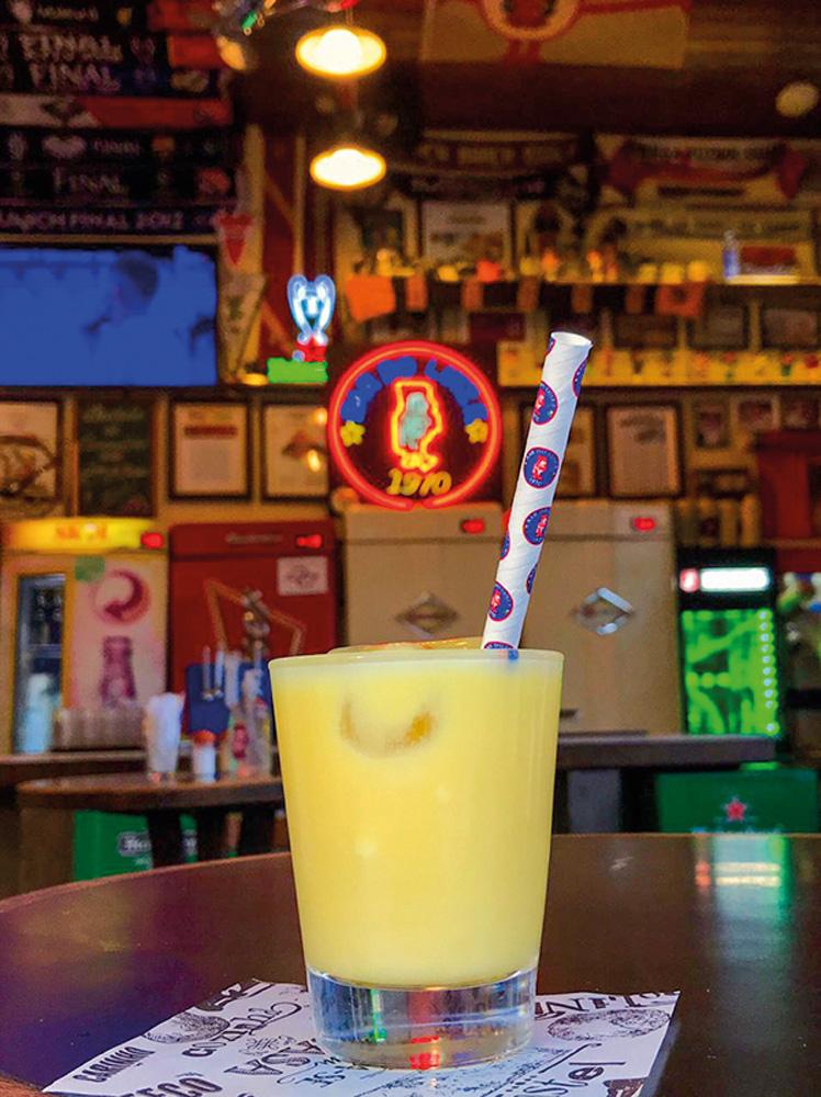 Batida amarela de curau em copo de vidro com canudo colorido sobre mesa de bar.