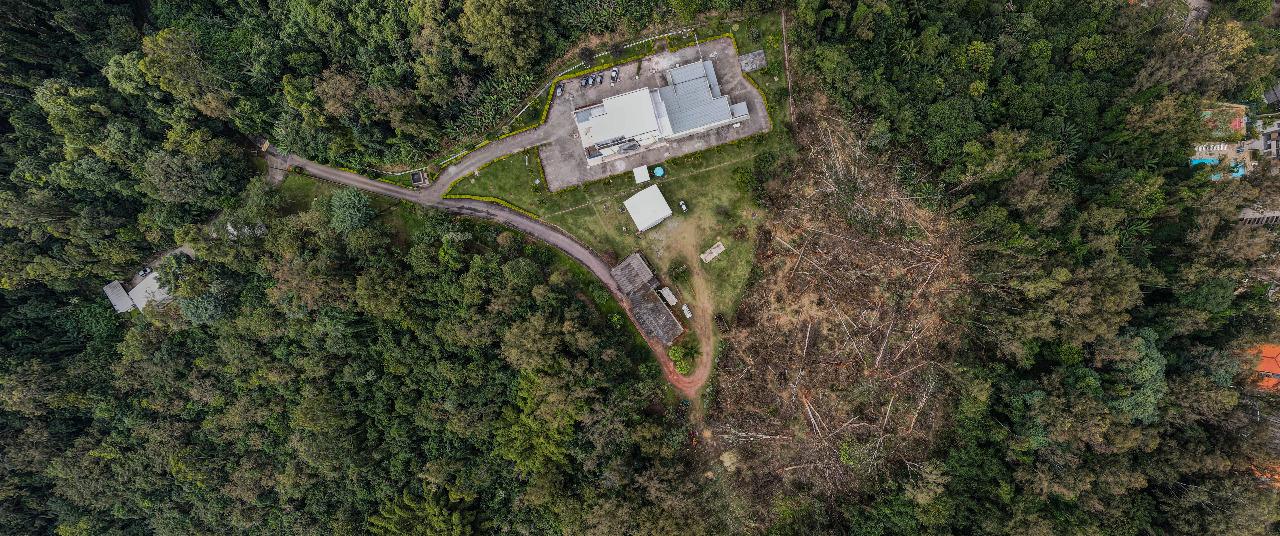 Imagem aérea mostra região coberta de mata, com edificação ao centro e, ao lado, área com árvores caídas no chão