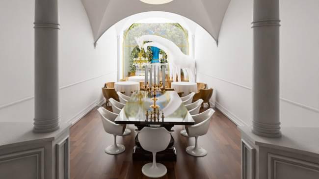 Projeção 3D do restaurante Lvtetia. Salão de paredes brancas com mesa retangular em destaque de tampo preto rodeada de cadeiras saarinen com braço brancas.