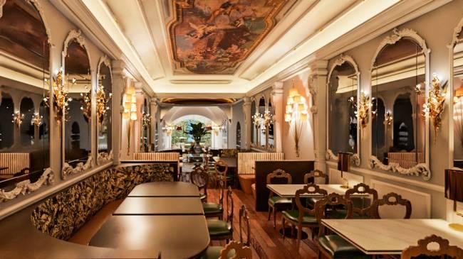 Projeção 3D do restaurante Lvtetia. Salão com pinturas no teto e espelhos nas paredes à esquerda e à direita. Mesas em ambos os lados ao longo do espaço.