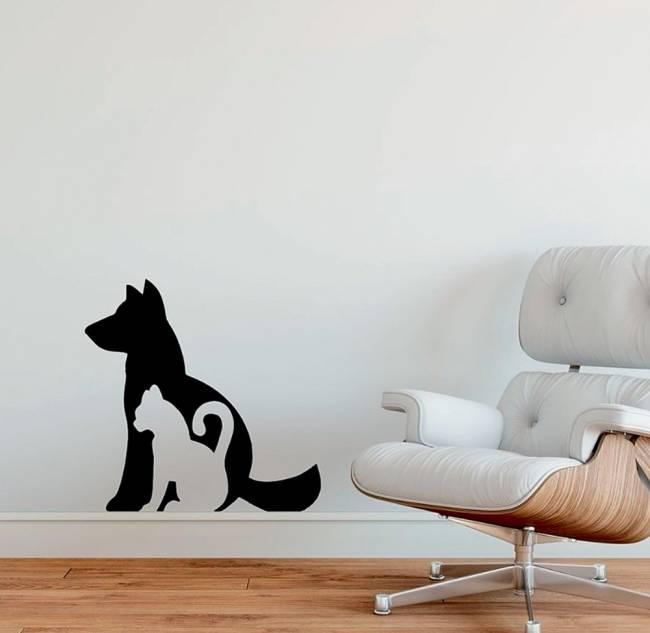 Uma parede tem um adesivo com a silhueta de cachorro e de um gato