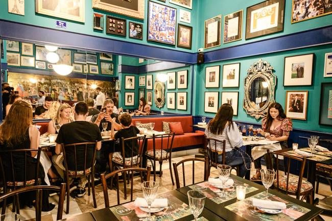 Salão do restaurante Ça-Va. Com paredes verde-água cobertas de quadrinhos e mesas com pessoas comendo em mesas nos cantos esquerdo e direito.