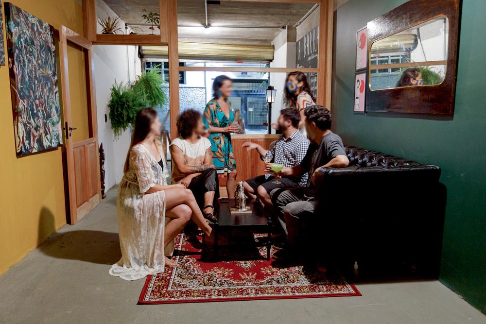 Pessoas sentadas em um sofá longo, conversando com outras duas sentadas em banquinhos.
