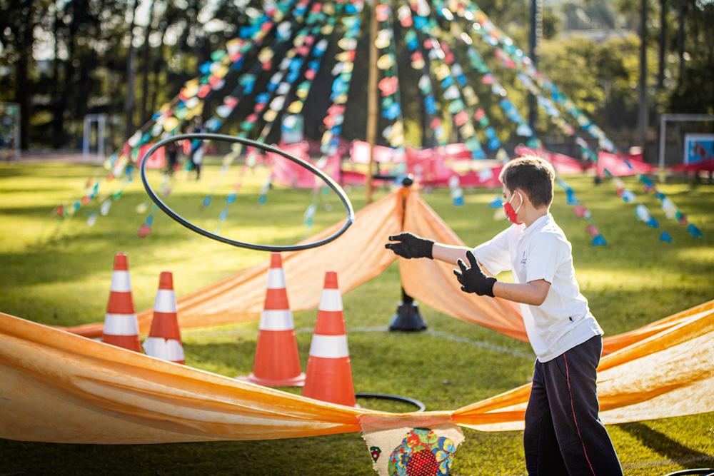 Uma criança joga um bambolê, que está no ar, em direção a quatro cones. Ao fundo, há bandeirinhas de festa junina