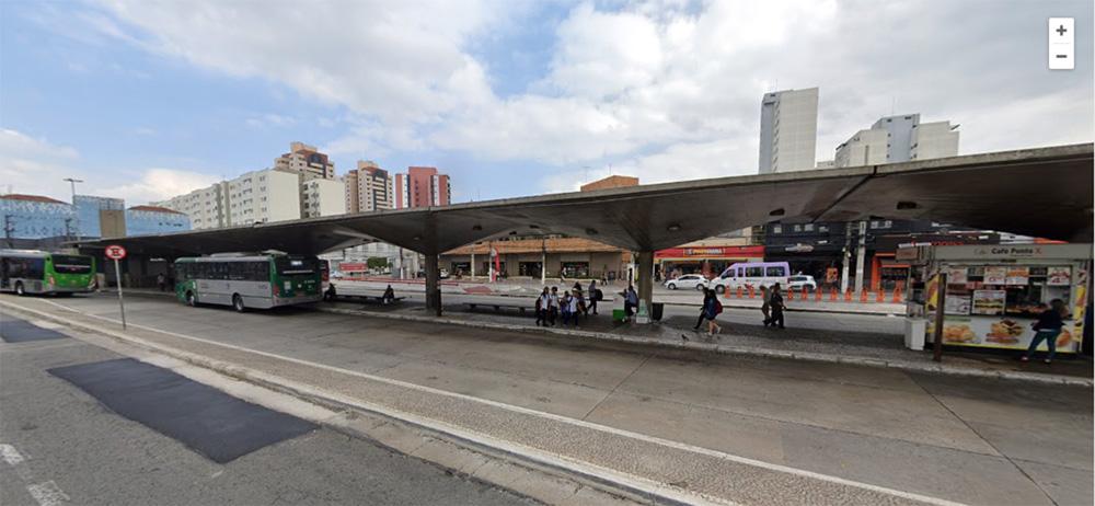 Foto mostra terminal de ônibus do Ana Rosa. Tem pessoas esperando ônibus