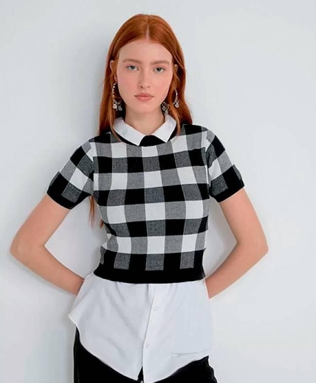 Jovem ruiva veste uma camisa branca, por cima, uma blusa xadrez preta e branca