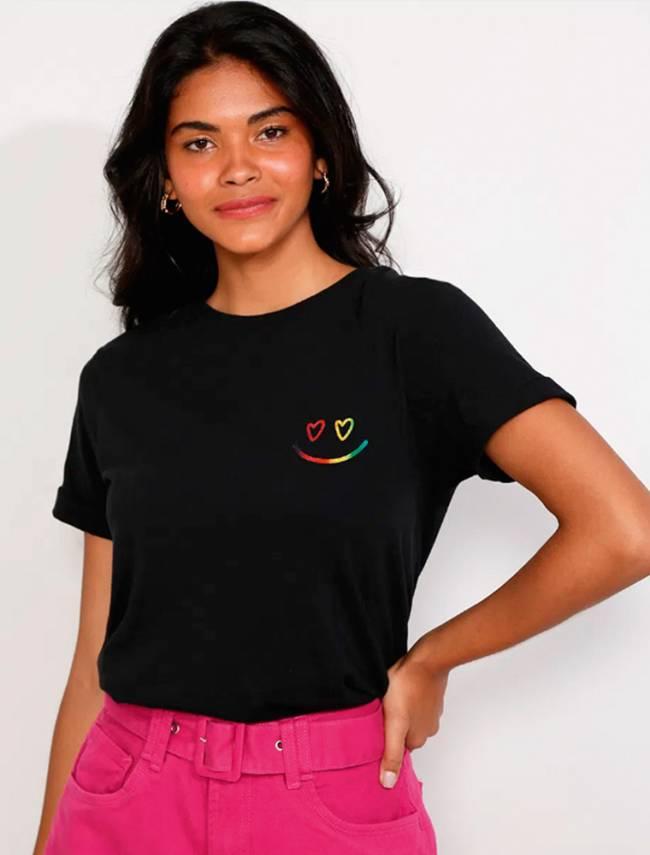 Menina veste camiseta preta com um emoji de sorriso nas cores da bandeira LGBT