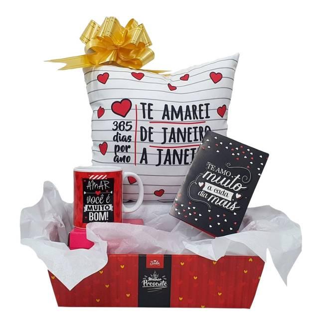 Uma caixa de presente com caneca de porcelana, cartão de amor e almofada. Nas cores vermelho branco e preto