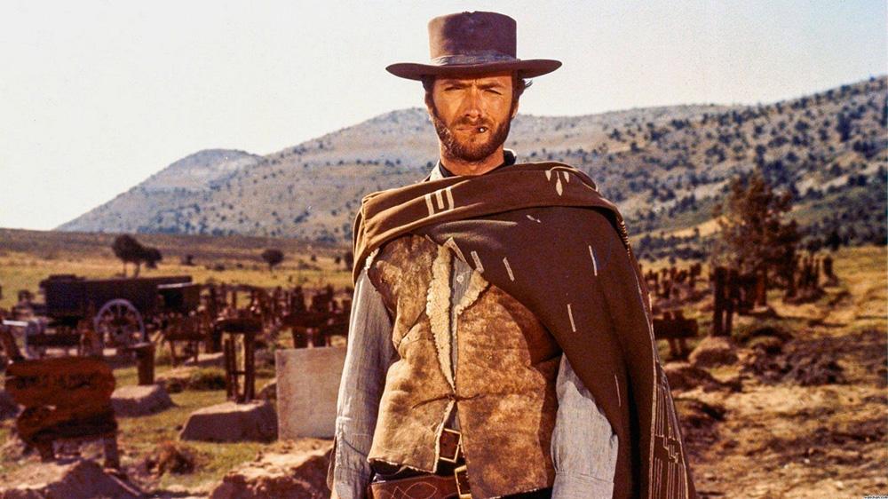 La foto mostra Clint nel selvaggio West, vestito da cowboy, che guarda la telecamera in una scena del film Tre uomini in conflitto