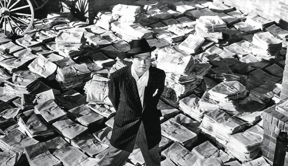 L'immagine del personaggio principale mostra il personaggio alto su una pila infinita di giornali