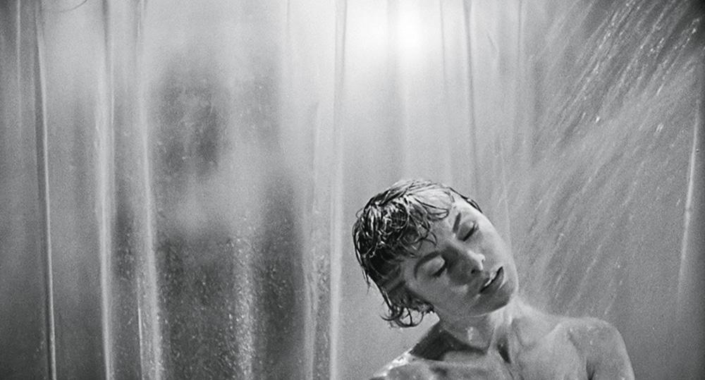 La foto mostra Janet Light sotto la doccia, dietro il suo telo trasparente, in una scena classica del film Psycho.