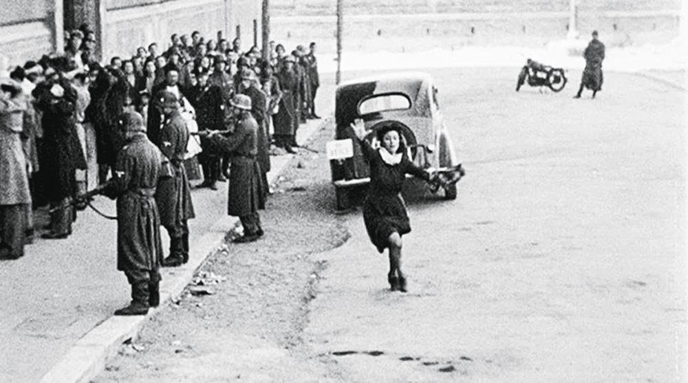 La foto mostra una strada piena di gente, con soldati e un bambino che corre in mezzo con la mano alzata.