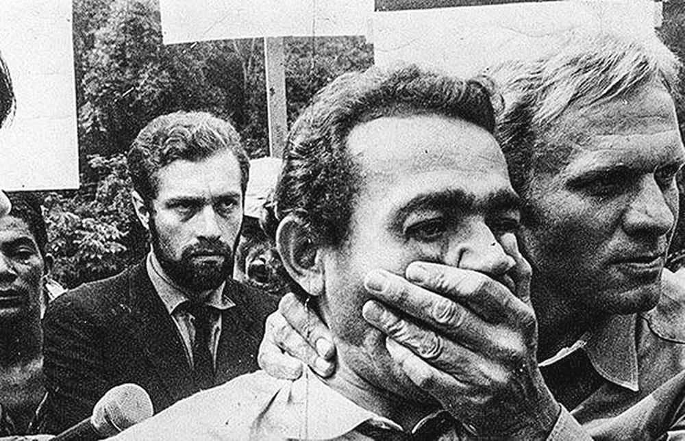 La foto mostra un uomo in mezzo alla folla, un altro uomo al suo fianco che si mette una mano sulla bocca, come se cercasse di coprirlo.