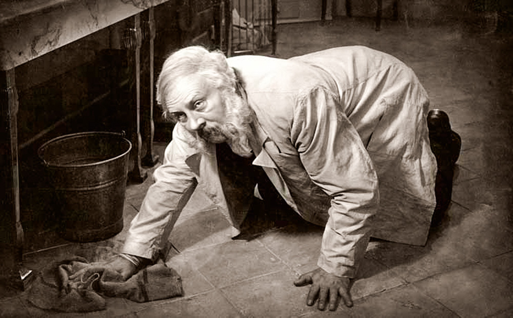 La foto mostra il porta-pellicola inginocchiato sul pavimento, che lo pulisce con uno straccio mentre alza lo sguardo con disapprovazione.