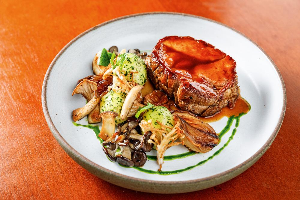 Em destaque, prato de interior branco sobre uma mesa de madeira. Nele, está um copa lombo glaceado ao lado de cogumelos, cebola e batatinhas do Clos Wine Bar.
