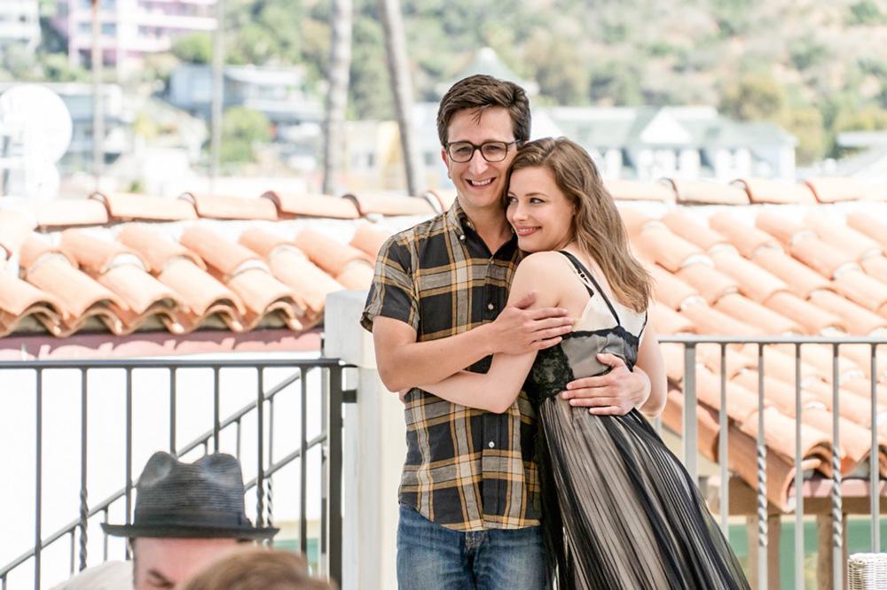 A imagem mostra Gillian e Paul abraçados, de pé, com ela apoiada sobre ele e ambos com sorrindo