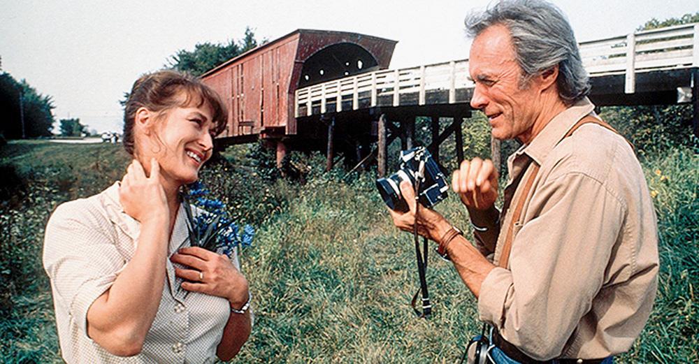 A imagem mostra Meryl e Eastwood, ambos rindo um para outro em uma região com muita vegetação próxima a uma estação de trem. Ele está com uma câmera na mãos.