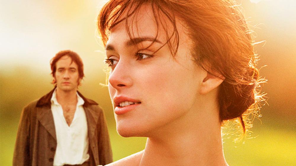 A imagem mostra Keira em um ambiente ensolarado olhando para o lado com Matthew ao fundo, um pouco desfocado