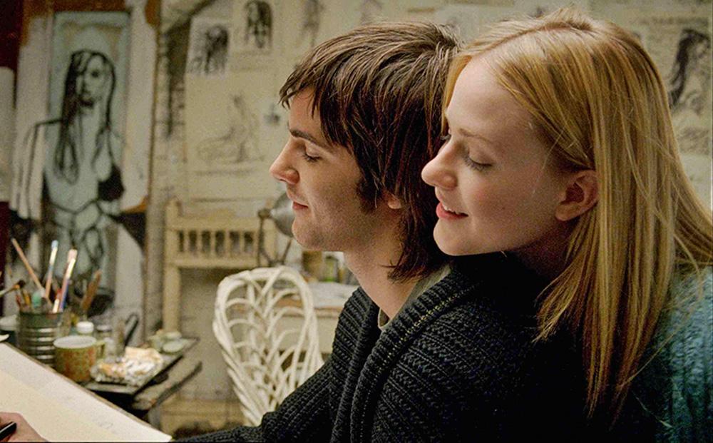 A imagem mostra o casal de Across the Universe, com uma mulher abraçando o homem por trás, ambos estão cantando, com ela com a cabeça sobre o ombro dele.