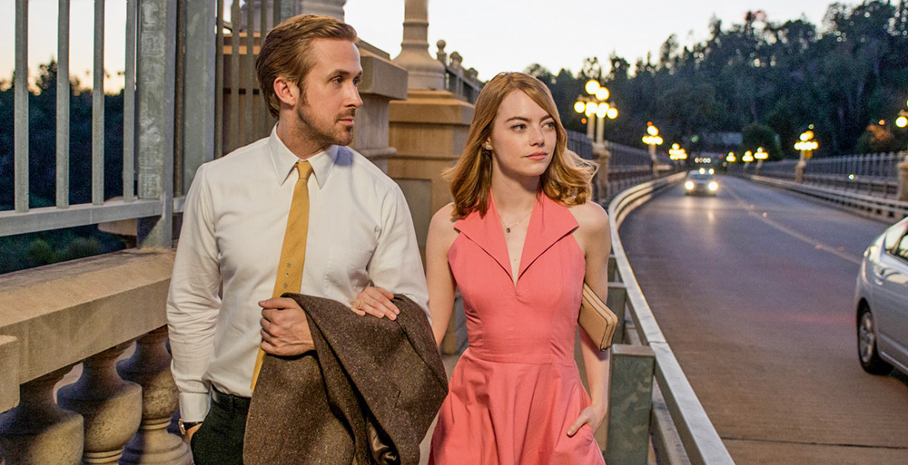Emma Stone e Ryan Gosling aparecem na imagem em cena do filme, andando de braços entrelaçados, olhando para a rua à esquerda deles