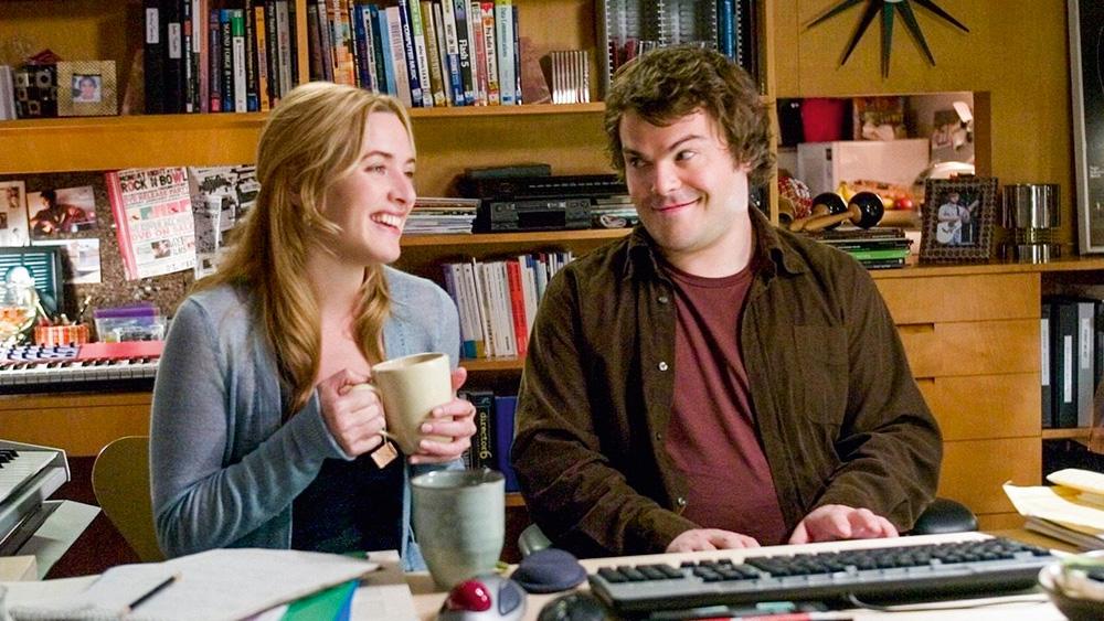 A imagem do filme mostra Jack olhando feliz com as sobrancelhas levantadas para Kate enquanto ela ri com uma xícara na mão.
