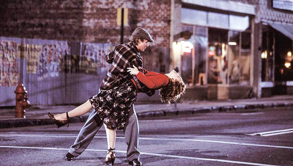 A imagem mostra Ryan Gosling e Rachel McAdams dançando na rua, com ele segurando ela com o braço direito enquanto ela faz o movimento de cair para trás.