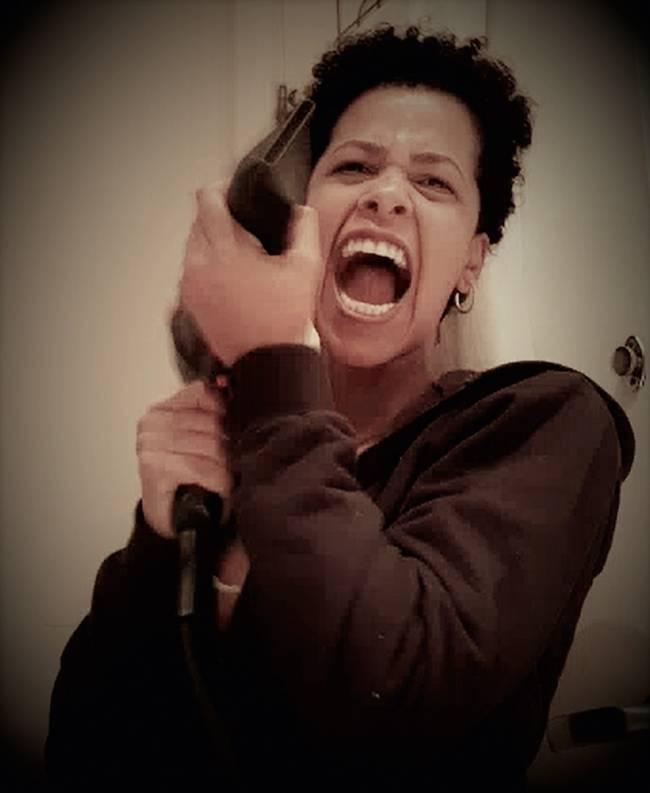 Mulher negra grita em foto segurando um secador de cabelo em movimento