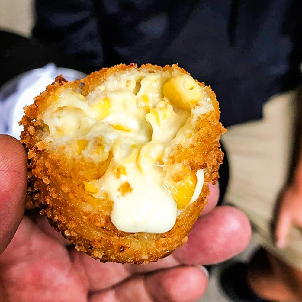 Mão segurando bolinho de milho mordido com queijo gorgonzola derretido.