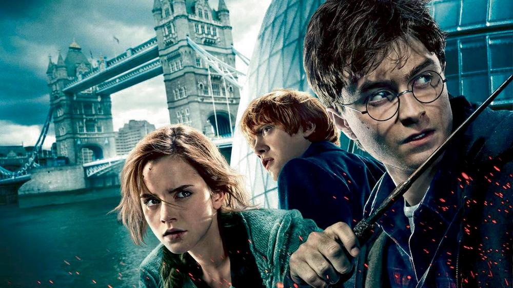 A imagem mostra os três protagonistas do filme Harry Potter com um castelo ao fundo, da ambientação do filme. Eles estão com uma expressão de seriedade.
