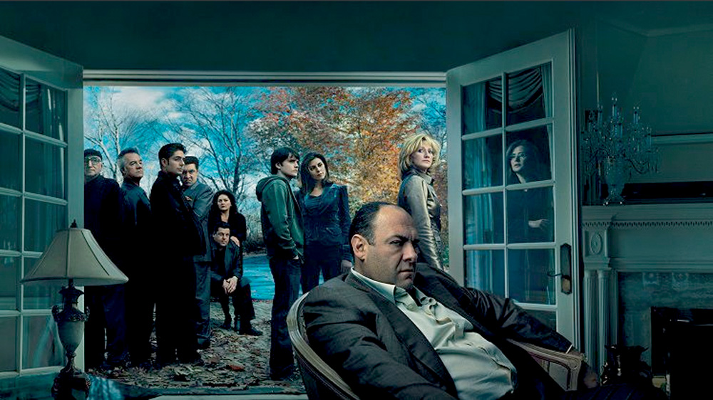 A imagem mostra os protagonistas de Os Sopranos em uma sala de uma casa. Todos com expressões sérias.