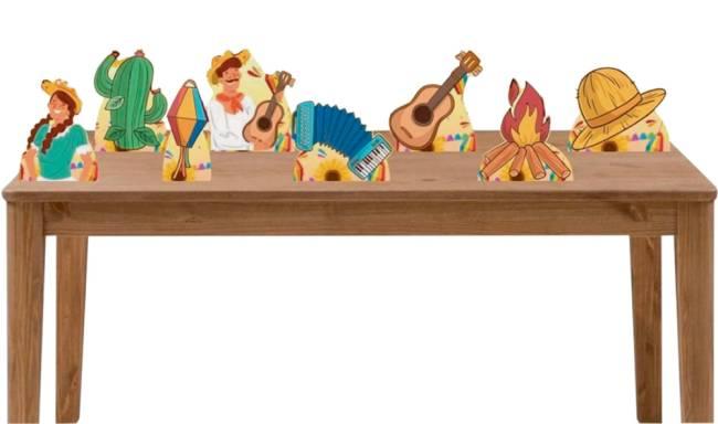 Uma mesa de madeira tem displays de desenhos de festa junina. Balão, fogueira, violão, chapéu de palha, cacto e homem e mulher