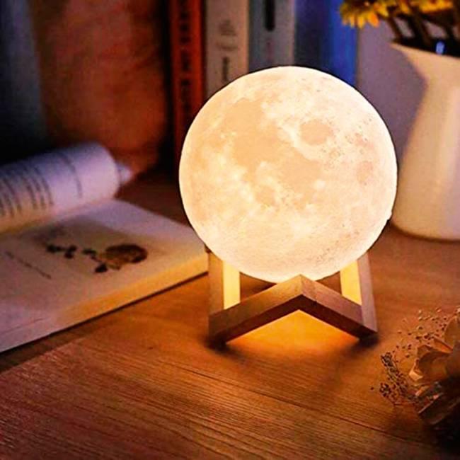 Luminária acesa em formato de lua. Está em cima de uma estante