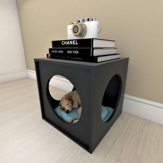 Uma mesinha de canto tem um espaço para um cachorro que está dormindo dentro. Em cima, livros e uma máquina fotográfica