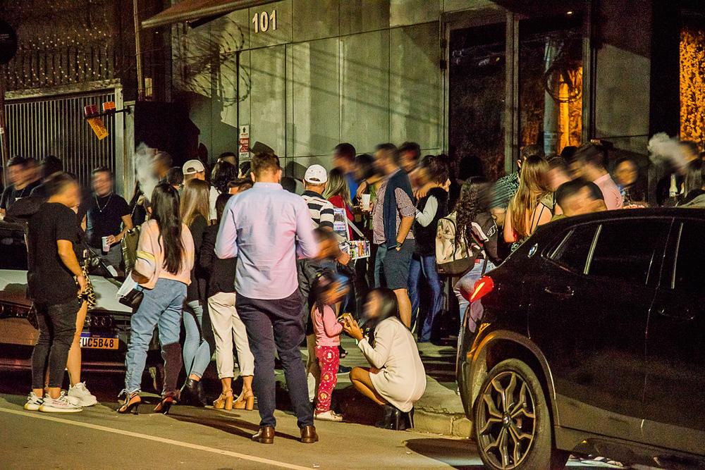 muitas pessoas bebendo e conversando em aglomeração de rua durante a pandemia no itaim bibi