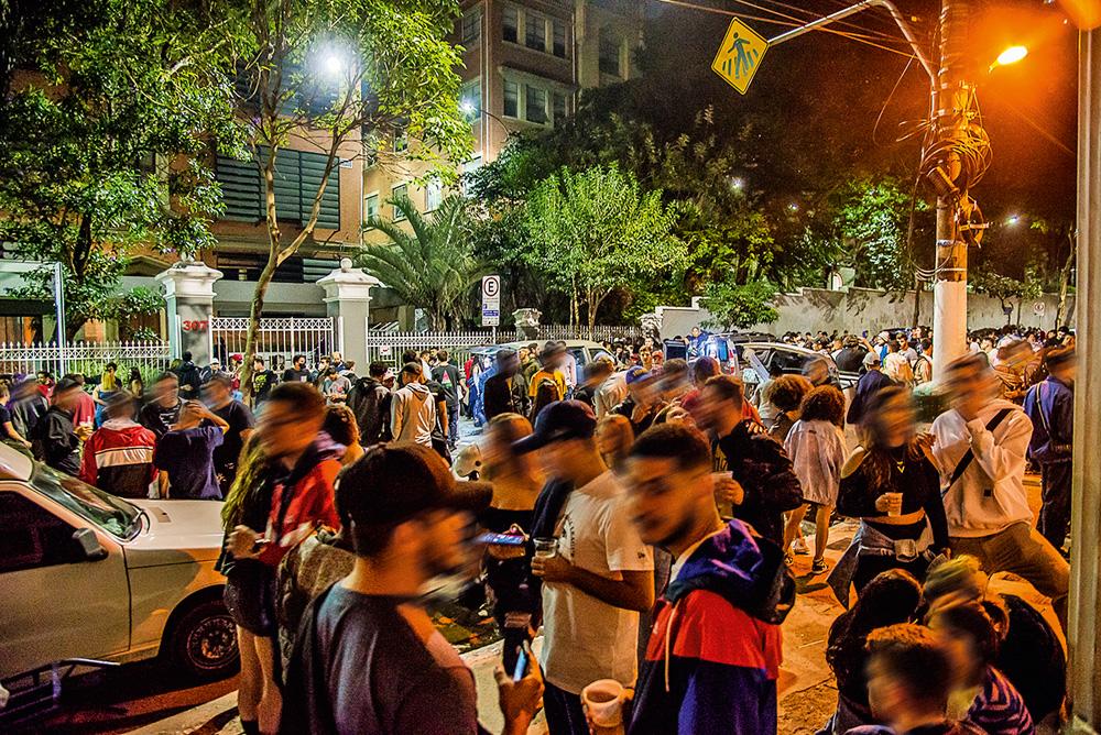 muitas pessoas bebendo e conversando em aglomeração de rua durante a pandemia na rua maria antônia