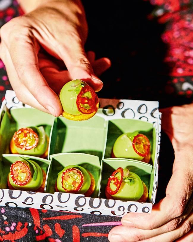 Foto de seis bombons de guacamole em caixa para delivery com divisão para cada um e uma mão oferecendo um deles.
